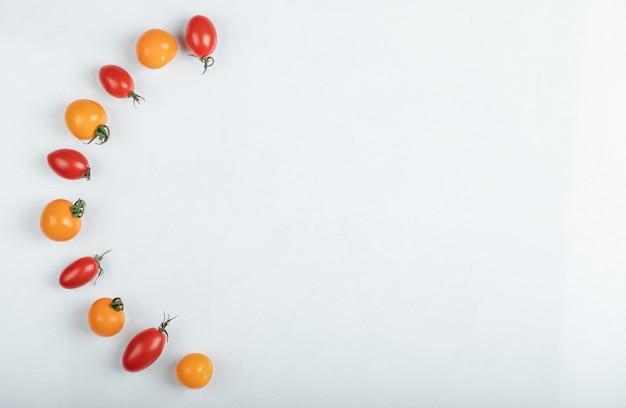 白地に広角キラリと光る赤と黄色のトマト。高品質の写真