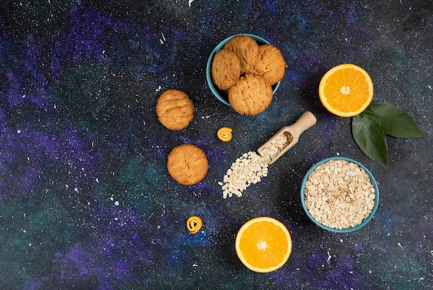 Wide angle photo of cookies with orange and oatmeal over space surface.