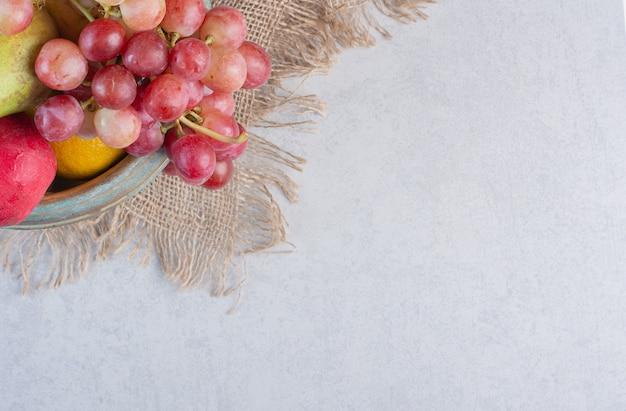 Foto grandangolare frutta organica fresca. mela, uva e mandarini sul sacco.
