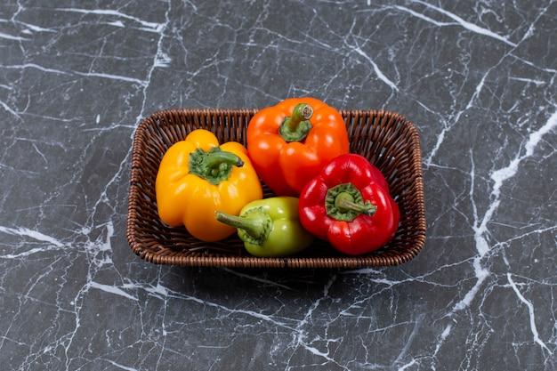 Широкоформатное фото свежие спелые болгарские перцы в плетеной корзине.
