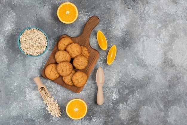 Foto grandangolare di biscotti fatti in casa su tavola di legno e farina d'avena con arance su superficie grigia.