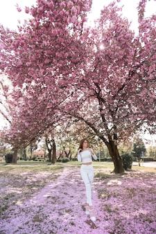 Широкоформатная фотография женщины в белых джинсах в розовом саду с деревьями, усеянными вишневыми цветами