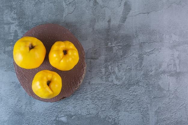木の板に新鮮なリンゴのマルメロの広角写真。