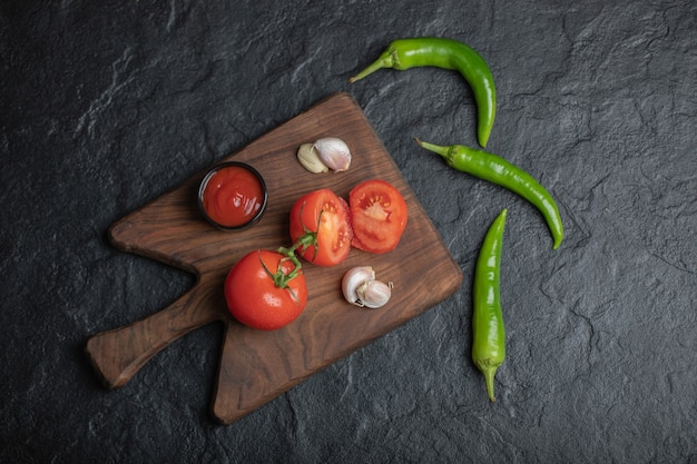 마늘과 케첩 나무도 마 보드와 검은 바탕에 녹색 후추와 잘 익은 토마토의 광각 사진.