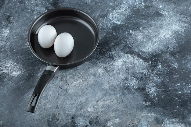 프라이팬에 두 개의 닭고기 달걀의 광각 사진