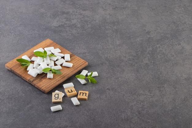 Foto grandangolare del mucchio di gomme bianche con foglie di menta sulla ciotola di legno