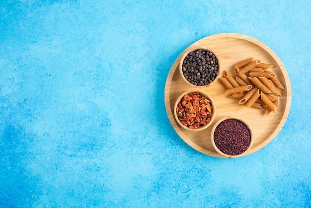 青いテーブルの上の木製トレイに広角写真スパイスと茶色のパスタ。