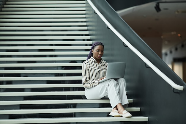 Wide angle portrait of african-american businesswoman in black and white outfit using laptop while sitting on stairs in office, copy space