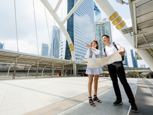 Wide-angle portrait cute smiling young asian couple tourists standing and holding a paper city map on footbridge together while woman pointing to destinations with tall building and sky background