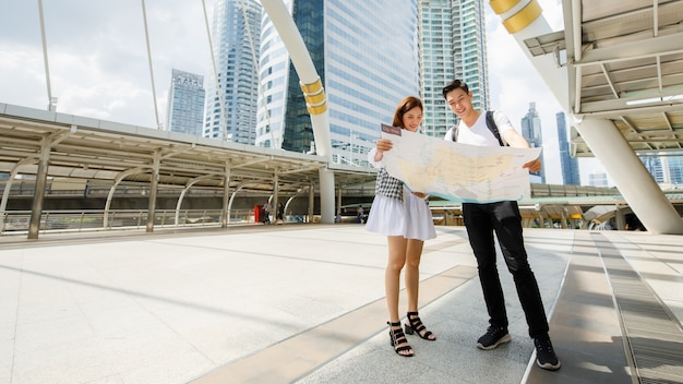 Wide-angle portrait cute smiling young asian lover travelers standing and holding a paper city map on footbridge together to find direction to destinations with tall building and sky background