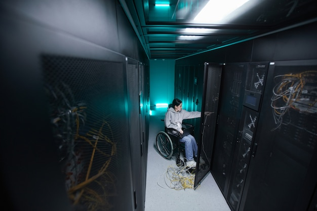 Wide angle portrait of disabled woman in wheelchair working with supercomputer network in server room, accessible job concept, copy space