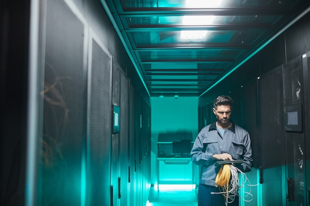 Wide angle portrait of mature network engineer using digital tablet in server room during maintenance work in data center, copy space