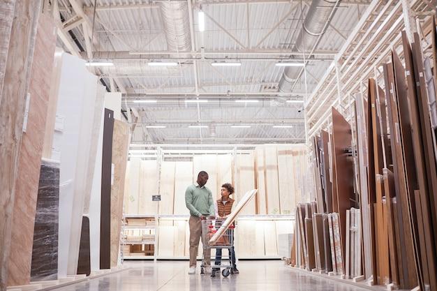 Широкоугольный портрет афро-американских отца и сына, делающих покупки вместе в строительном магазине, стоящего с тележкой на острове из дерева и досок, копировальное пространство