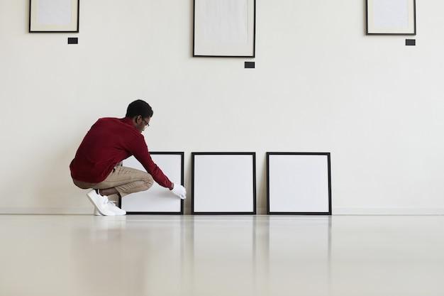 아트 갤러리 또는 전시회를 계획하는 동안 바닥에 빈 검은 색 프레임을 설정하는 아프리카 계 미국인 남자의 광각 초상화,