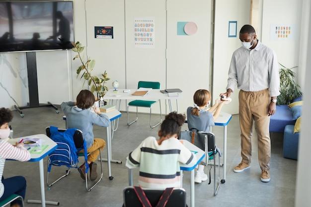 학교 교실에서 아이들의 손을 소독하는 아프리카계 미국인 교사의 광각 초상화, 코비드 안전 조치, 복사 공간