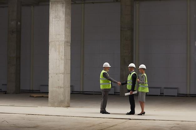 실내 건설 현장에서 투자 거래를 논의하면서 악수하는 사업 사람들의 광각 초상화,