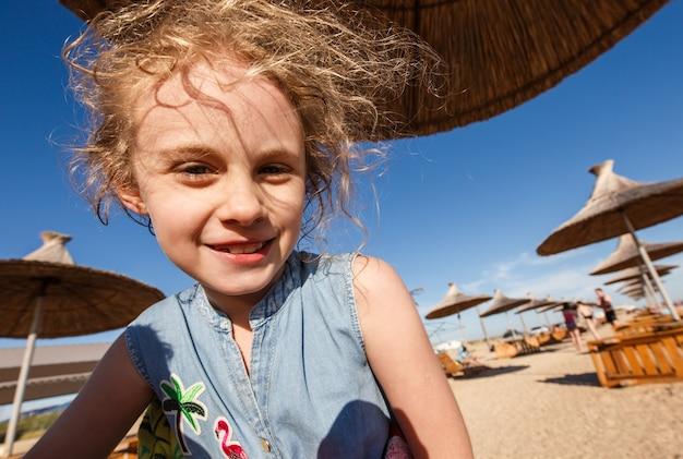 夏のビーチで陽気な子供の女の子の広角の肖像画。