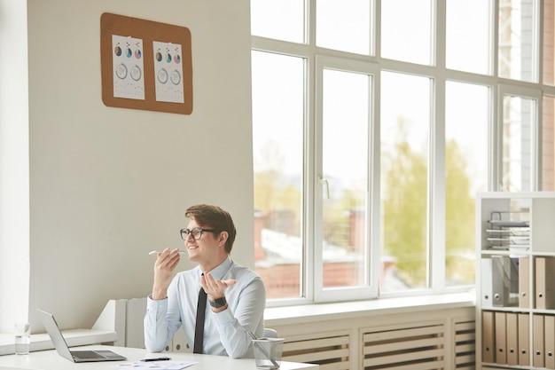 Широкоугольный портрет веселого молодого бизнесмена, записывающего голосовое сообщение через смартфон, сидя за столом в белом интерьере офиса, копировальное пространство