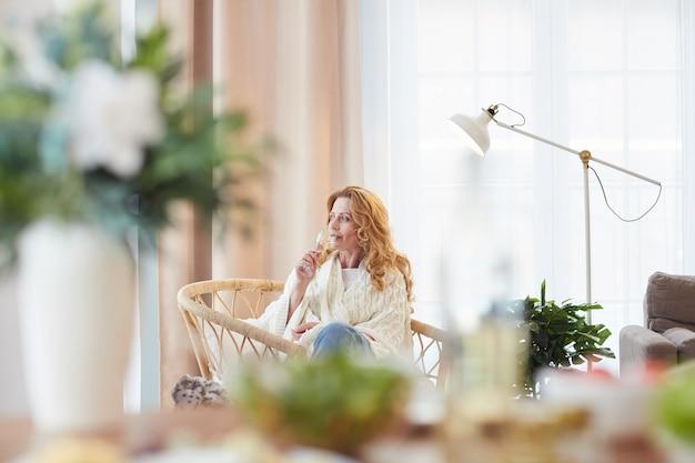 집에서 어슬렁 어슬렁 어슬렁 어슬렁 거니는 동안 멀리보고있는 동안 샴페인을 즐기는 우아한 성숙한 여인의 광각 초상화, 복사 공간