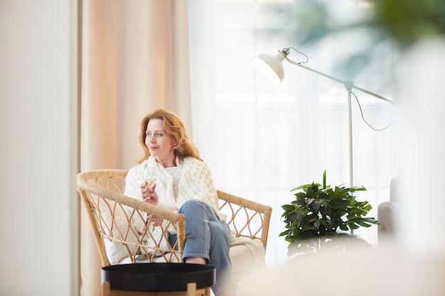 집에서 휴식을 취하고 pensively 멀리보고있는 동안 샴페인을 즐기는 우아한 성숙한 여자의 광각 초상화, 복사 공간