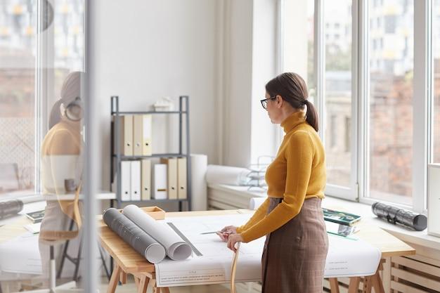 사무실에서 책상에 서있는 동안 blueprings를 그리기 여성 건축가의 와이드 앵글 초상화,