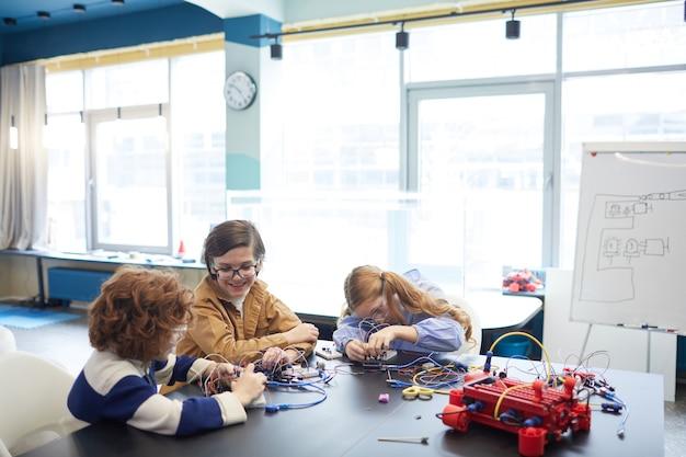 Широкоугольный портрет трех детей, строящих роботов на уроке инженерии в школе развития, копировальное пространство