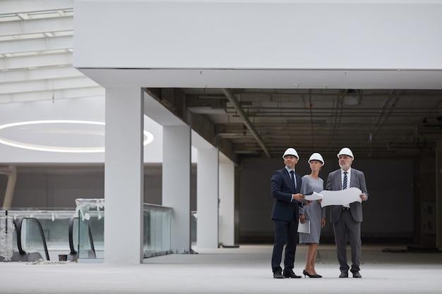 안전모를 착용하고 실내에서 건설 현장을 검사하는 동안 계획을 잡고있는 세 명의 성공적인 비즈니스 사람들의 광각 초상화,