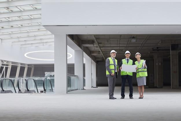 Hardhats를 착용하고 실내 건설 현장에 서있는 동안 올려 세 성공적인 사업 사람들의 광각 초상화,