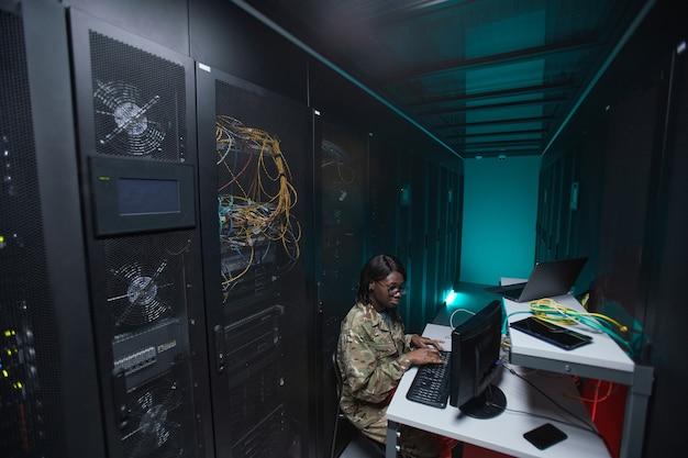Широкоугольный портрет молодой афро-американской женщины в военной форме, использующей компьютер при настройке сети в серверной комнате, копией пространства