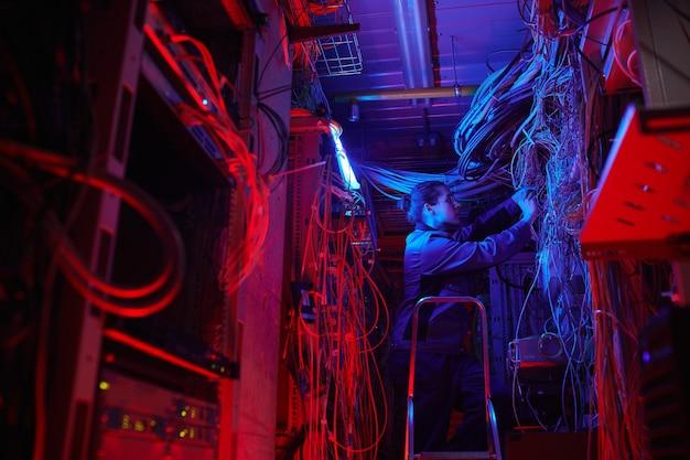 Широкоугольный портрет молодого человека, устанавливающего компьютерную сеть в серверной с кабелями и проводами, копией пространства
