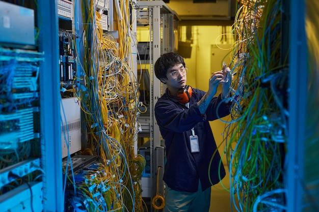 Широкоугольный портрет молодого специалиста по сетям, соединяющего провода и кабели в серверной комнате, освещенный синим светом, копировальное пространство