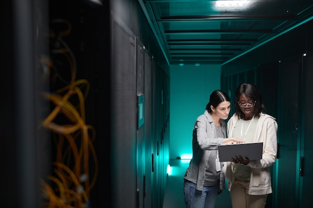 Wide angle portrait of two female it engineers setting up server network while working in data center, copy space