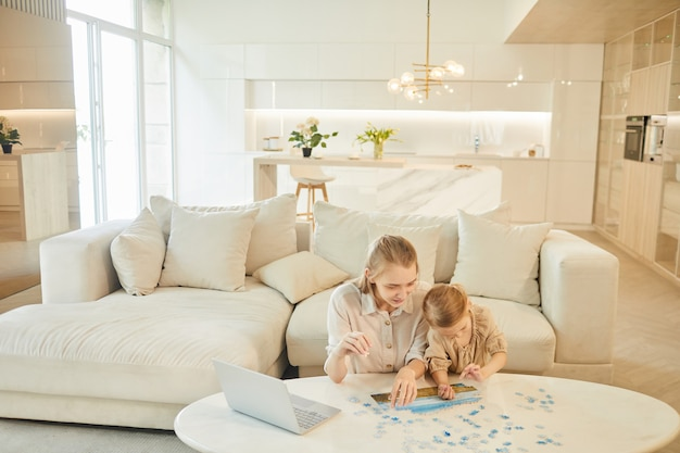 Wide angle portrait of two sisters solving puzzle together while enjoying time at home indoors in white interior