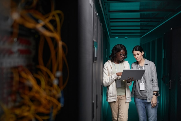 Wide angle portrait of two young women using laptop in server room while setting up supercomputer network, copy space