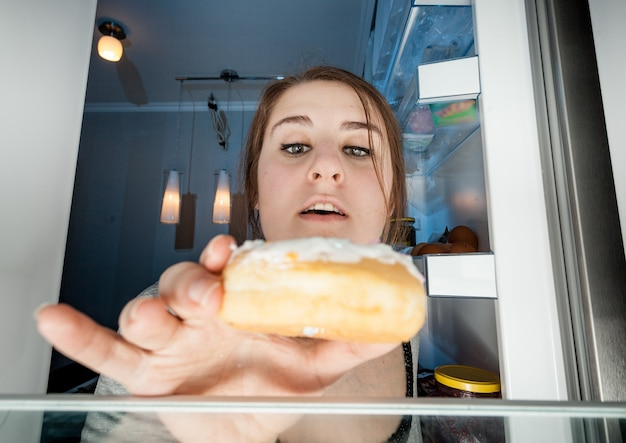 Wide angle portrait of woman taking donut from fridge