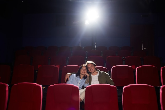 Wide angle portrait of young loving couple in cinema watching movie while enjoying romantic date, man embracing girlfriend, copy space