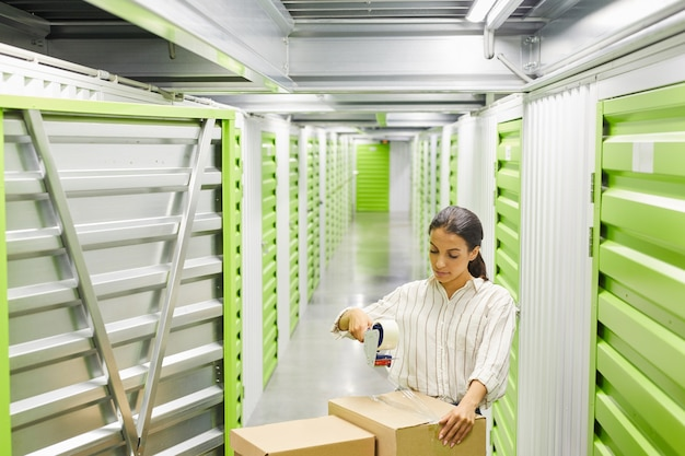 Wide angle portrait of young woman packing boxes with tape gun while standing by self storage unit, copy space