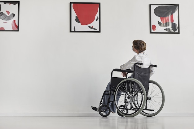 Wide angle portrait of young woman using wheelchair looking at paintings in modern art gallery,