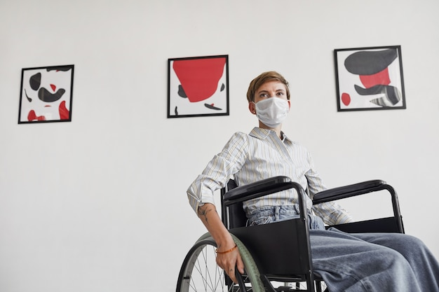 Wide angle portrait of young woman using wheelchair and wearing mask while looking at paintings in modern art gallery