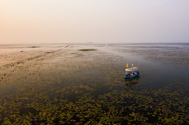 Wide angle shot of a boat in the lotus lake in thailand