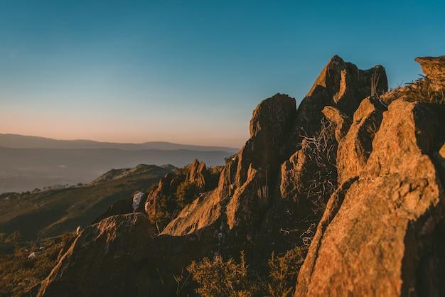 Colpo grandangolare di una scogliera su una montagna sotto il sole e un cielo blu chiaro