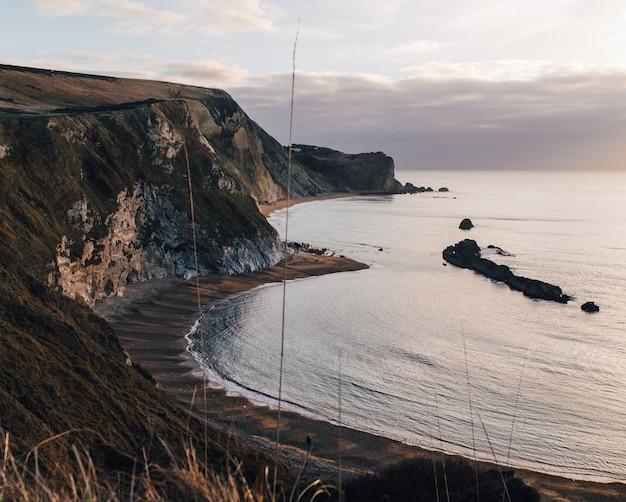 Colpo grandangolare delle scogliere e delle rocce della spiaggia