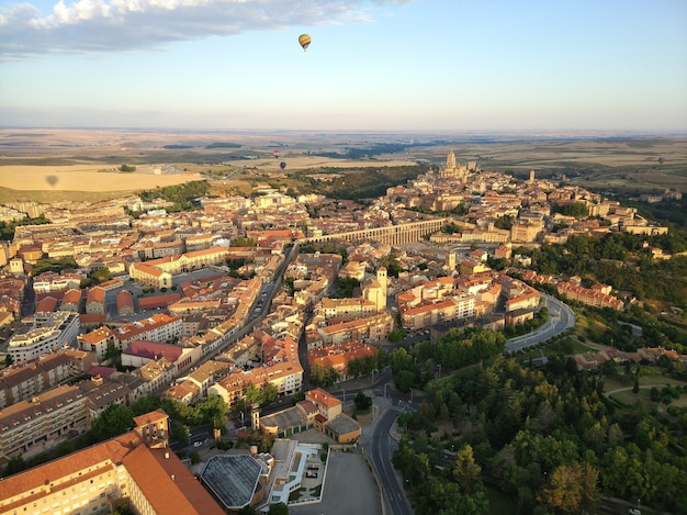 Wide angle shot of many buildings surrounded by trees and a parachute up in the air