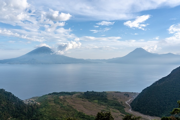 Wide angle shot of the mountains in front of the ocean under a clear blue sky  in guatemala