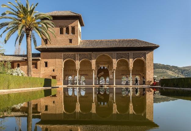 물 앞과 스페인의 나무 옆에있는 건물의 와이드 앵글 샷
