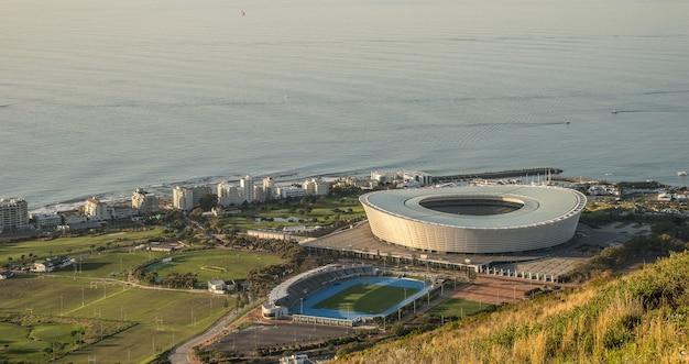 Широкоугольный снимок круглого стадиона и других зданий вокруг поля у океана.