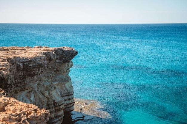 Широкоугольный снимок скалы у океана в дневное время