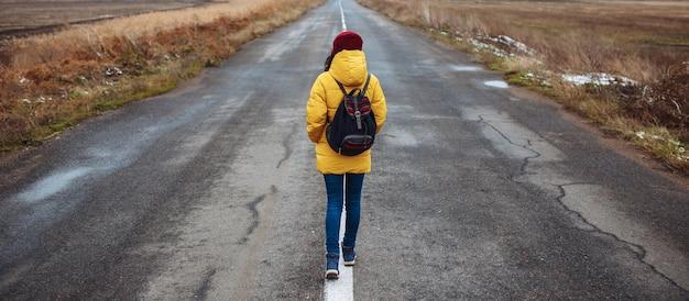 黄色いジャケットと赤い帽子をかぶったバックパックを持った女性観光客の広角ショットが道路を歩きます。
