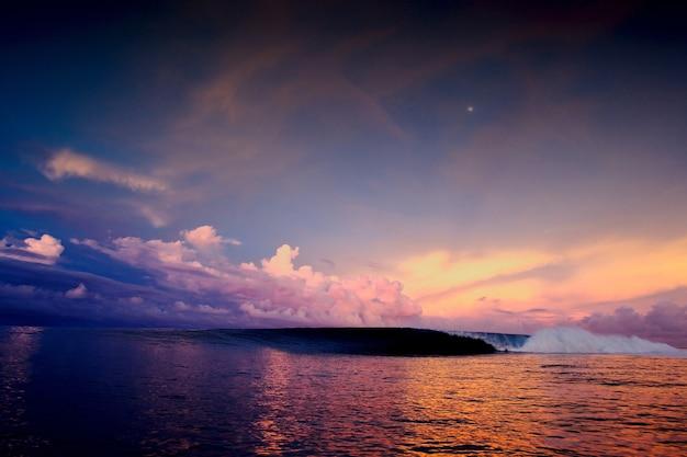 여러 가지 빛깔의 구름이 가득한 하늘 아래 바다에서 매혹적인 일몰의 와이드 앵글 샷