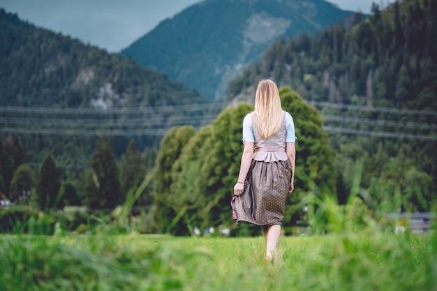 Широкоугольный снимок женщины в юбке и галстуке, идущей к горам